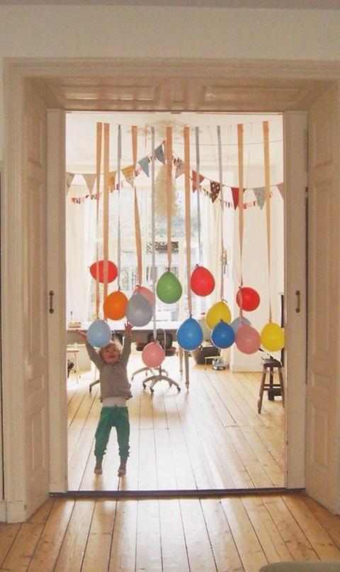 Verjaardag kleuter met slinger van ballonnen aan deur